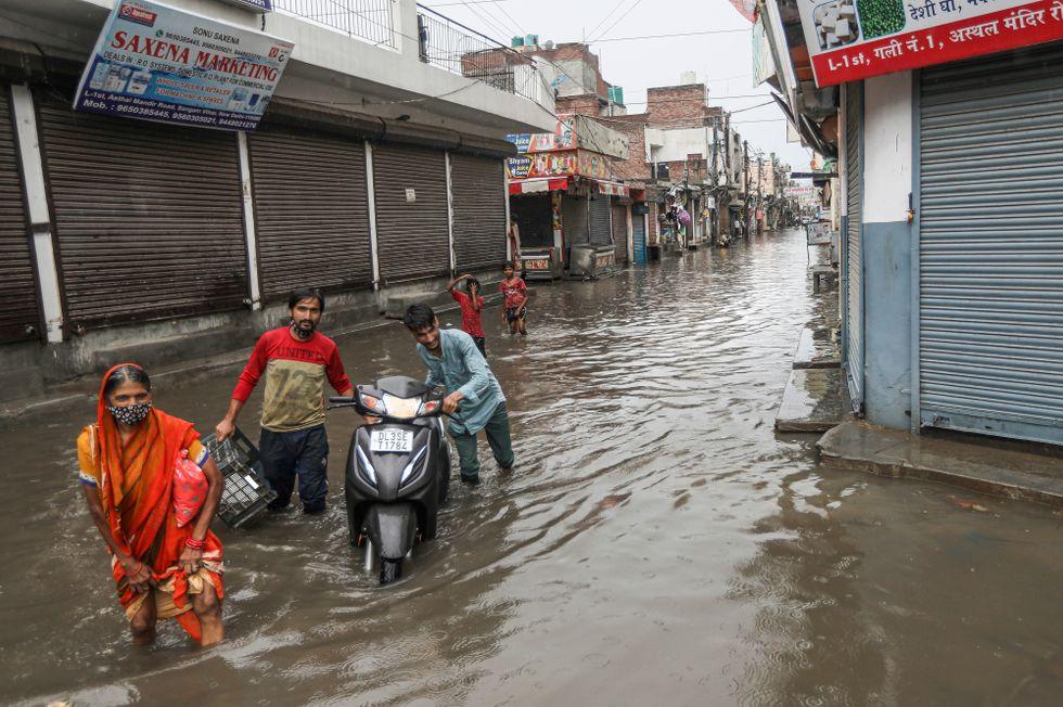 Människor vadar genom New Delhi, Indien efter ett monsunregn.