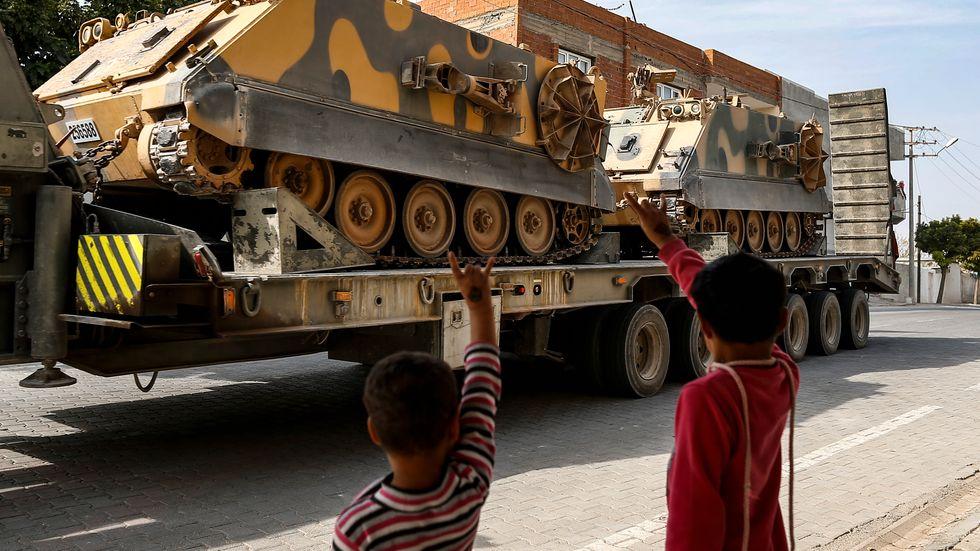 Barn vinkar till turkiska styrkor på väg till syriska gränsen den 15 oktober.