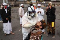 Vårdpersonal testar människor för coronaviruset på östra Java.