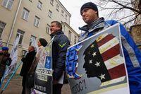 """Människor protesterar mot den ryska valobservatörsorganisationen Golos utländska förbindelser. Plakaten har texter som """"Utländska agenter har inget i Ryssland att göra""""."""