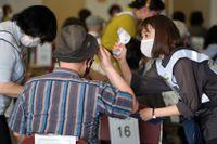 Kroppstemperatur kollas vid ett vaccineringscenter i Tokyo på måndagen.