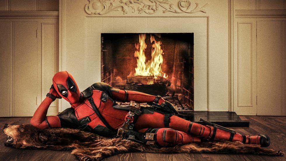 Ryan Reynolds poserar framför brasan.