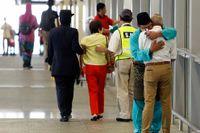 Mannen i blått förlorade sin familj i flygkatastrofen. Han tröstar en annan man som kom till flygplatsen i Kuala Lumpur för att få bekräftat att hans dotter omkommit.