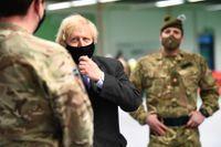 Storbritanniens premiärminister Boris Johnson träffar soldater som jobbar med att bygga upp ett vaccionationscenter i Glasgow i Skottland.