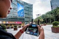 DJI:s chefspilot Ella Lv demonstrerar DJI Mavic Pro –företagets första hopfällbara drönare – utanför bolagets huvudkontor i Shenzhen. För den som inte vill släpa med sig kontrollen kan drönaren också styras med enbart en smartphone.