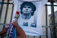 En man hänger en ros på en t-shirt föreställande Diego Maradona i samband men en protestmarsch i Buenos Aires i mars 2021. Många kräver fortsatt svar på om allt gick rätt till i samband med fotbollslegendarens död. Arkivbild.