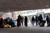 Migranterna utanför Malmö stadshus har tagit skydd från regnet vid en cykel- och gångbana under en bro.