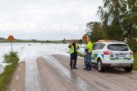 Personal från kommunen vid översvämmad väg i Getinge.