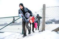 Migranter går genom snön i Lipa-lägret i nrordvästra Bosnien, vid gränsen till Kroatien.