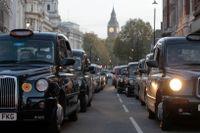 Klassiska taxibilar på rad vid Trafalgar Square i London.