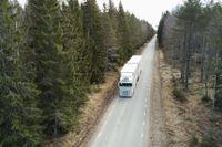 En lastbil på en asfalterad landsväg mellan granarna i en skog i norra Uppland.