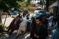 Kabulbor hjälper talibanpoliser med en trasig polisbil.