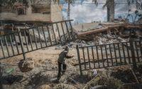 Ett palestinskt barn i Gaza inspekterar resterna av ett bostadshus som förstörts av israeliska bomber.