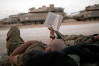 En israelisk soldat öäser en bok under vapenfilan.