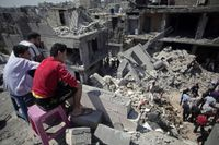 Palestinier söker i rasmassorna efter att åtta människor mist livet i flyktinglägret tidigare under morgonen.