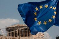 En EU-flagga framför templet Parthenon i Aten. Arkivbild.
