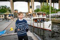Olof, 9 år, och ångbåten Blidösund i bakgrunden.