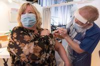 """Jens Stenbro ger Catharina Ahlsten hennes första dos mot covid-19. Hon tycker att proceduren fram till vaccinationen i Filadelfiakyrkan har varit """"jättesmidig""""."""