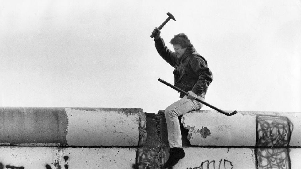 En man hackar frenetiskt på den mur som sedan 1961 delat Berlin i två delar, november 1989.
