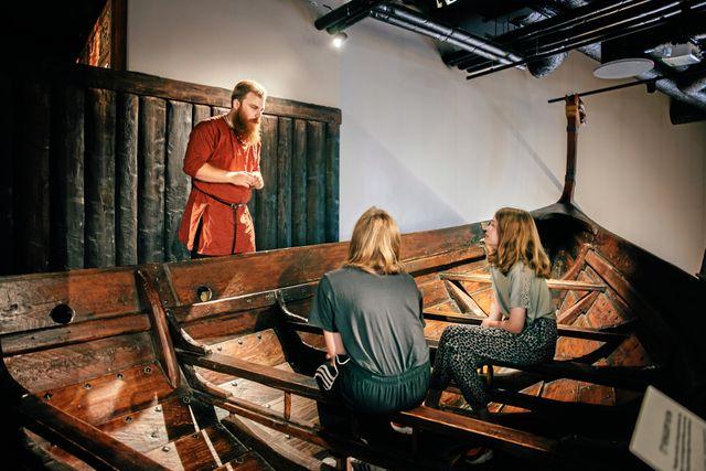 Vikingarna har gjort sig kända för sina båtar och sin långa resor med dessa runt om i världen. Här är en sådan båt som tjejerna sitter i medan Eric berättar fler vikingahistorier. Foto: Adam Wrafter