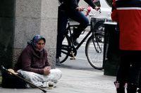 En romsk kvinna som tigger på en gata i Stockholm.