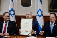 Israels premiärminister Benjamin Netanyahu håller upp den amerikanska kungörelsen, signerad av Donald Trump. Arkivbild från 14 april.