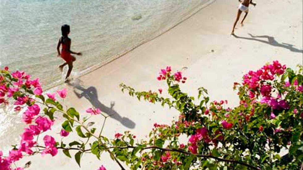 Barn leker på strand på Mauritius.