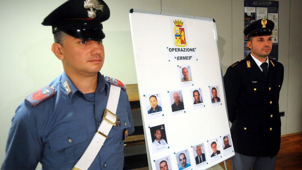 Italiens polis intill ett plakat med foton på personer som misstänkts ha hjälpt sicilianska maffian. Arkivbild.