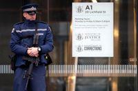 En polis vaktar ingången till domstolsbyggnaden i Christchurch, där misstankarna mot den 28-årige Brenton Tarrant presenterades.