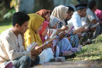 Sörjande ber vid en gravplats för tsunamioffren i Banda Aceh i Indonesien under torsdagen.