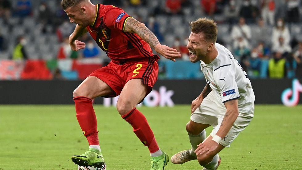 Italiens spelare Ciro Immobile (till höger) i närkamp med Belgiens Jan Vertonghen i kvartsfinalen på EM-arenan i München. Immobile blev liggandes på planen och vred sig i synbara smärtor men återhämtade sig mirakulöst snabbt när Italien gjorde mål sekunderna efteråt.