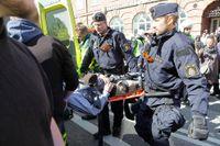 Polis bär en skadad demonstrant till ambulansen.