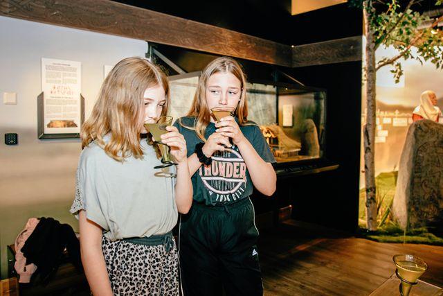Hedda och Wilma får smaka på mjöd som var en vanlig dryck under vikingatiden. Foto: Adam Wrafter