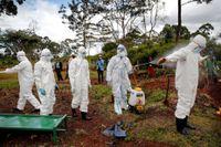 En grupp som begraver offer för coronaviruset desinfecerar sig själva i Nairopi.
