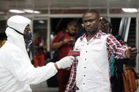 Personal mäter passagerarnas temperatur med en digital termometer på Murtala Muhammed International Airport i Lagos, Nigeria.