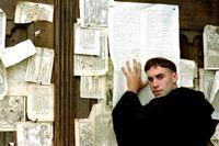 """Martin Luther, spelad av Joseph Fiennes, spikar upp sina teser på porten till slottskyrkan i Wittenberg i filmen """"Luther"""" (2003)"""