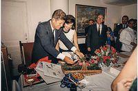 President Kennedys födelsedagsfest 29 maj 1963 i Vita husets Navy Mess Hall. Presidenthustrun Jackie Kennedy läser födelsedagshälsningar med sin make.