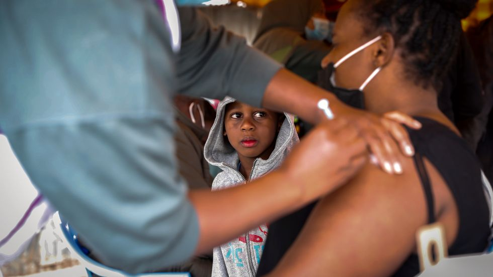 En kvinna i Kenya får en dos covidvaccin från Astra Zeneca som donerats av Storbritannien. Bilden togs i augusti.