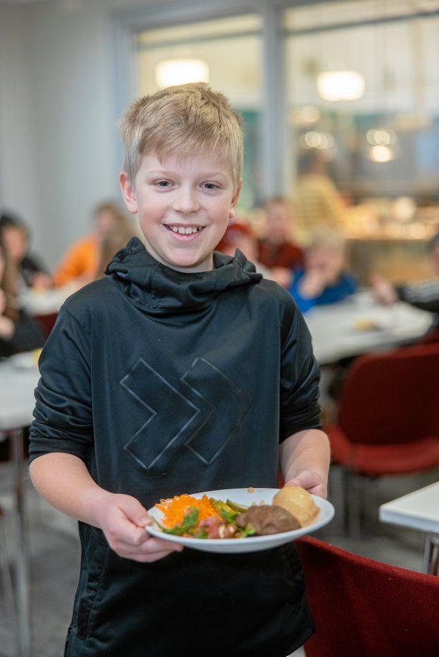 """Det har tillkommit nya regler i matsalen på grund av pandemin. Sam och hans klasskompisar sitter tillsammans och med """"coronaavstånd"""" mellan varandra vid borden."""