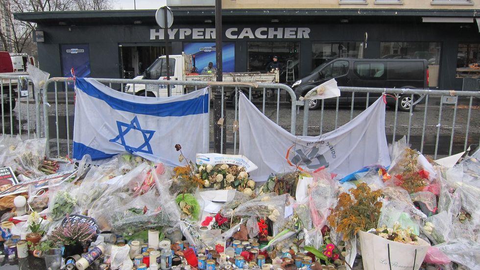 Blombuketter, skyltar och brev omgärdar kosherbutiken Hyper Cacher i sydöstra Paris där fyra judar föll offer för den militanta islamisten Amedy Coulibaly i terrorattentatet den 9 januari 2015.
