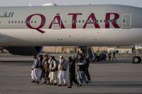 Talibaner promenerar förbi det plan som lyfte från Kabuls flygplats på torsdagen.