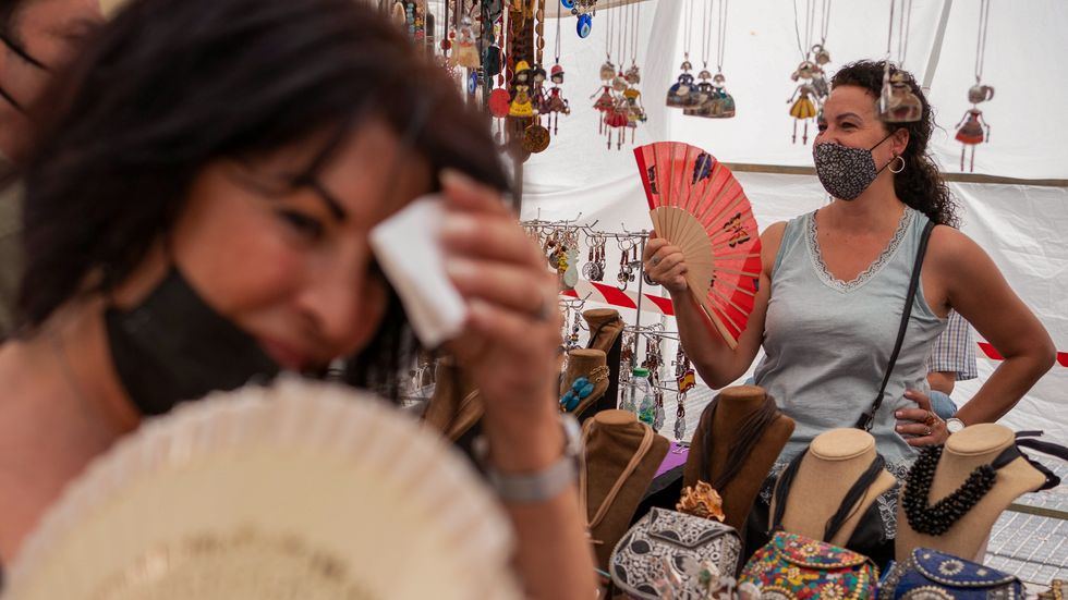 Kvinnor söker svalka på en marknad i Madrid. Värmen i landet har satt nytt rekord.