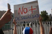 """En demonstrant håller upp en skylt med texten """"Ingen mer ojämlikhet"""" under protester utanför presidentpalatset La Moneda i Chiles huvudstad Santiago i lördags."""