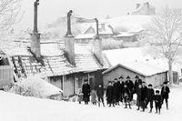 Vinterbild från Vita Bergen norrut, tagen någon gång mellan 1885 och 1895. Vuxna och barn med kälke vid Lilla Mejtens Gränd 4. Då hade motståndet mot kälkåkning lättat. Tidigare hade det funnits perioder då det till och med var straffbart att åka kälke.