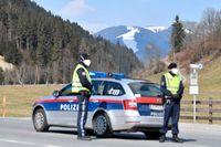 Österrikisk polis bevakar en väg mot skidorten Saalbach 2 april.