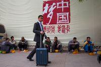 """""""Kinas dröm"""" står det på väggen bakom byggnadsarbetare som har lunchpaus på en gata i Peking. (Arkiv)."""