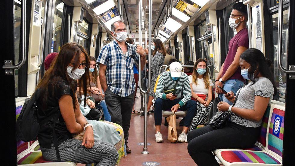 Resenärer bär munskydd på tunnelbanan i Paris den 13 juli.