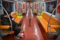 En ensam resenär på en i vanliga fall full tunnelbanelinje i Peking.