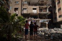 Palestinier i flyktinglägret Shati i Gaza betraktar byggnaden som bombades av Israel. Tio människor dödades i attacken.