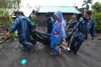 Räddningsarbetare bär en man som drunknade när tyfonen Goni drog fram över Guinobatan i den filippinska provinsen Albay.